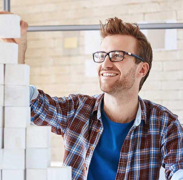Man building blocks in office environment