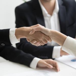 Handshake between two people in formal work setting