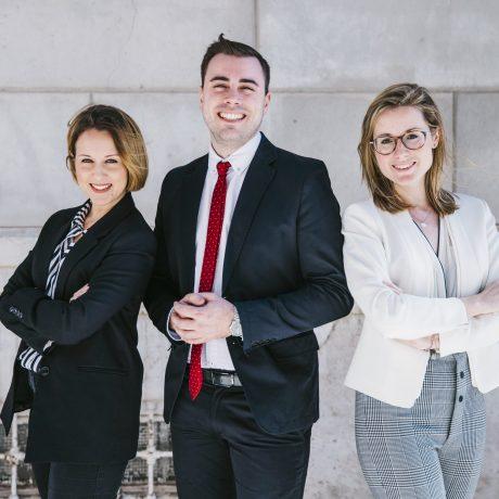 Team in formal work attire smiling into camera