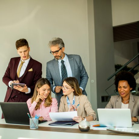 Group-of-business-people-working-in-an-office-around-one-large-desk