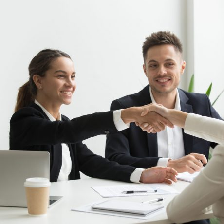 Smiling HR managers greeting female job applicant with handshake during recruiting or interview. Businesswoman making good first impression shaking hands of business partners. Partnership, cooperation